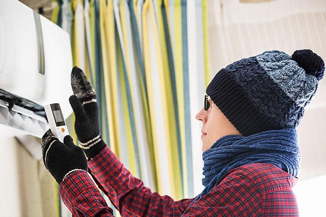 エアコンを暖房にする男性