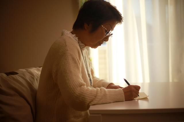 手紙を書くシニア女性