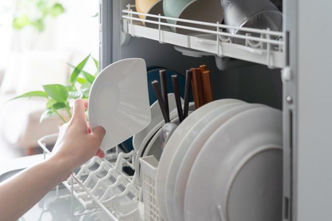 食洗機に皿を入れる女性
