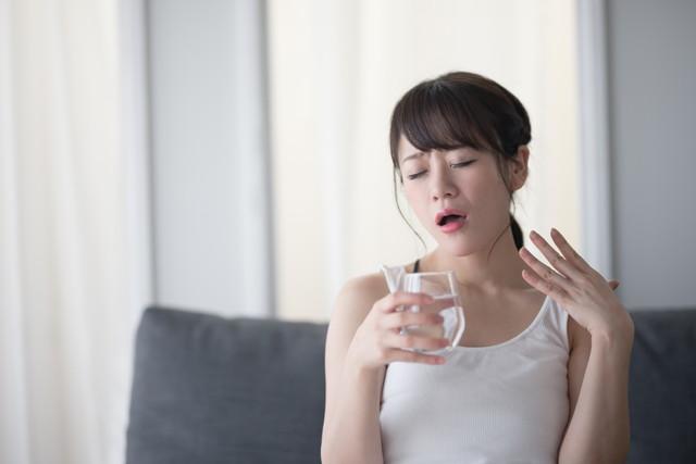 暑くて水を飲もうとしている女性