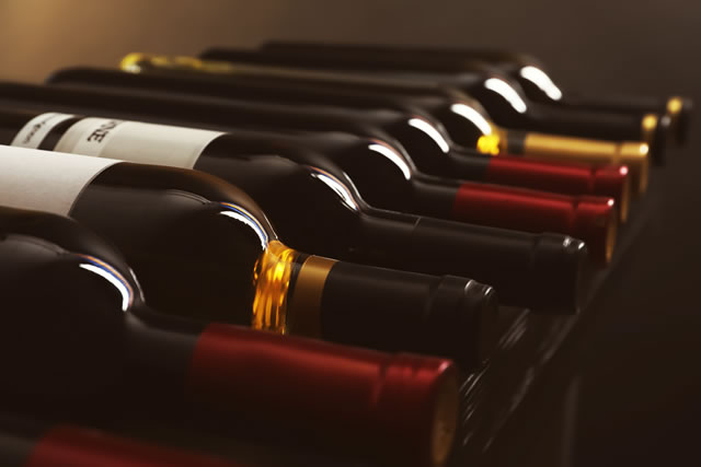 Bottles with delicious wine on shelf, closeup. Professional sommelier
