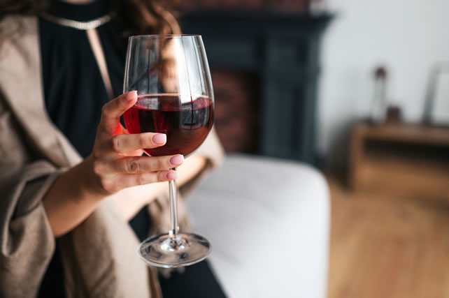 Cut view of woman's hand holding glass of red wine. Model wear black dress and brown shawl. Woman in living room alone.