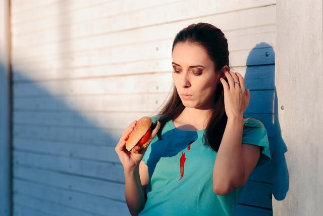 ケチャップソースと彼女のシャツを染色不器用な女性
