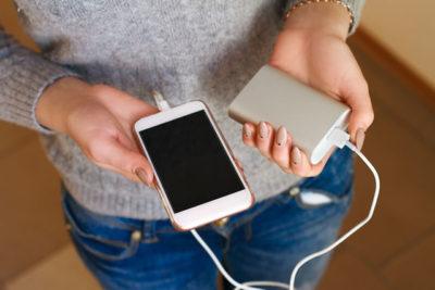 スマホとモバイルバッテリーを持っている女性