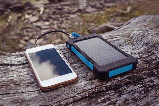 モバイルバッテリーとスマホが木の上に置いてある