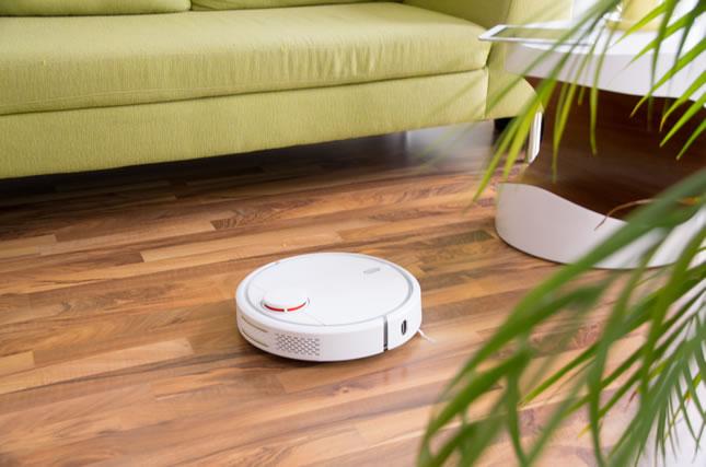 Staubsaugerroboter im Wohnzimmer auf Parkettboden