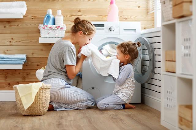 女性と子供が洗濯機で洗濯