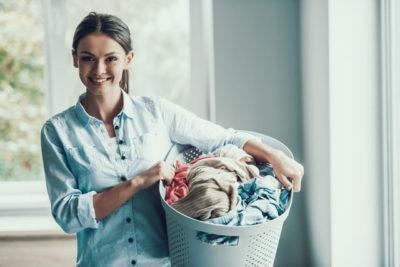 女性が洗濯物を抱える