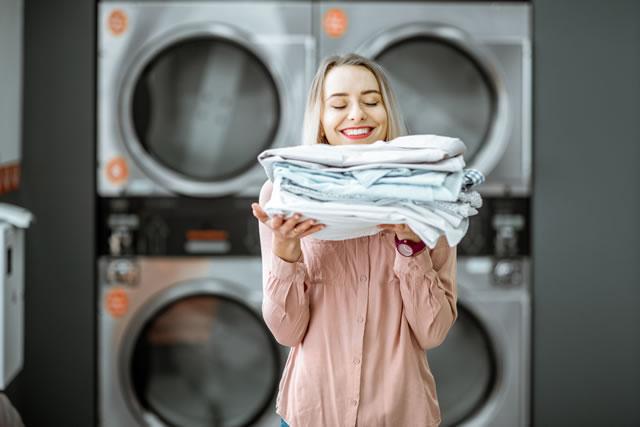洗い終わった洗濯ものを持つ女性