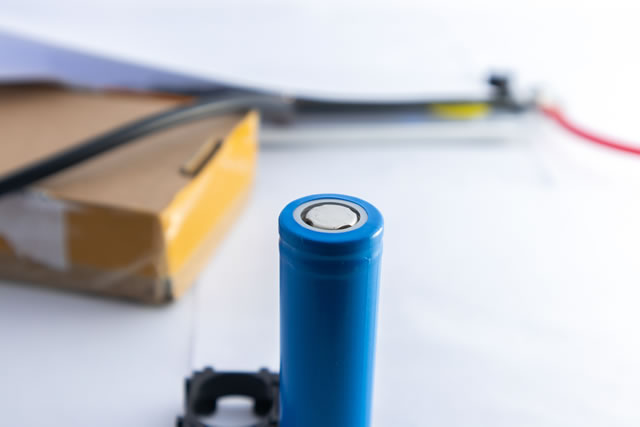 Blue lithium ion battery which placed vertically with blurred background.