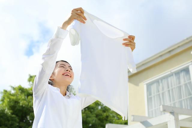 笑顔で洗濯物を干す女性