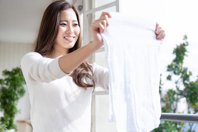 洗濯物を持つ笑顔の女性