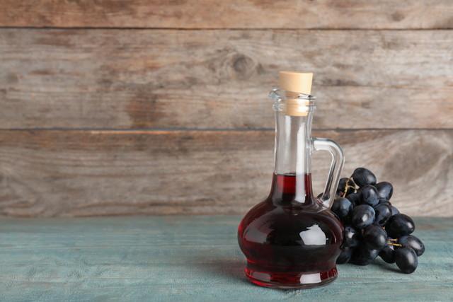 ワイン酢と木製のテーブルに新鮮なブドウのガラスの水差し