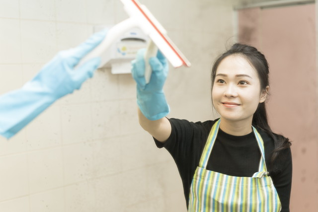 トイレの汚れた鏡を掃除する女性