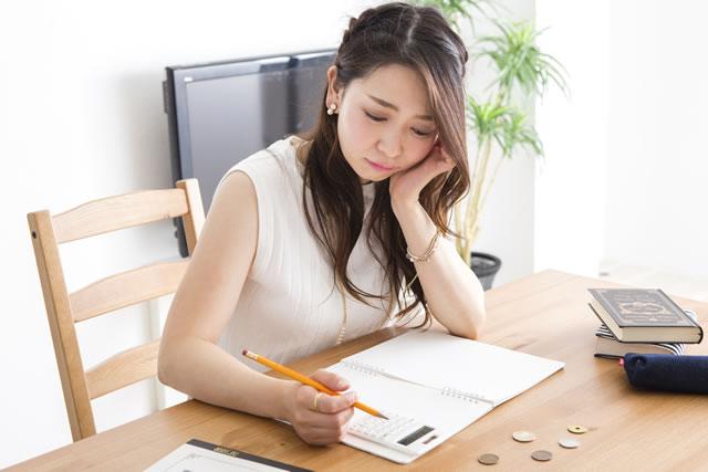 暗い表情で家計簿を見る女性
