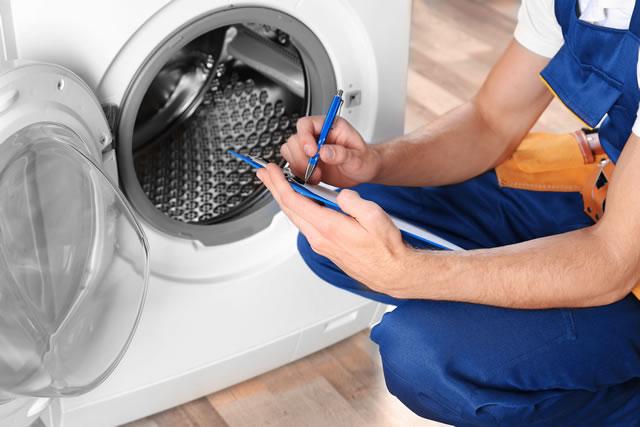 洗濯機のチェックをする男性