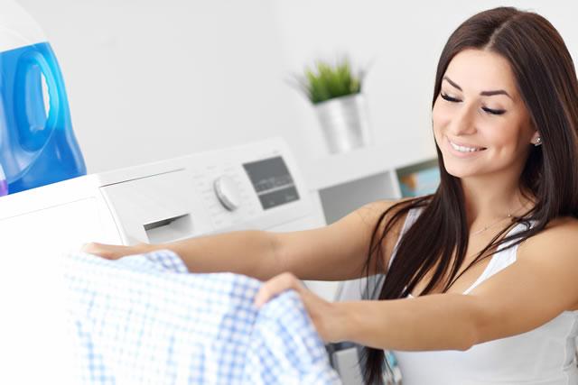 笑顔で洗濯物に手を掛ける女性