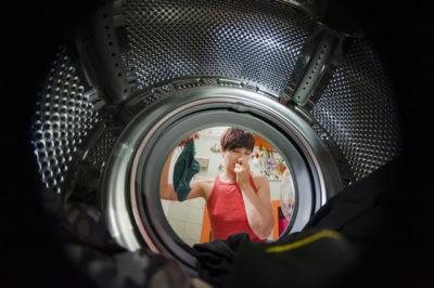 洗濯機の臭いをかぐ女性