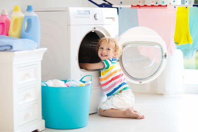 笑顔で洗濯物を取り出す子ども
