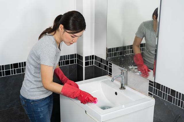 流し台を洗う女性