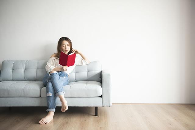 一人でソファに座りくつろぐ女性