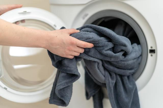 燥機から毛布を取り出す腕