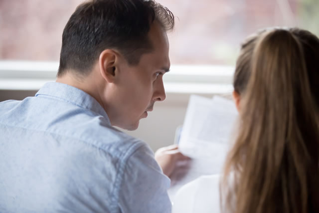 真面目な表情で手紙を見つめる夫婦