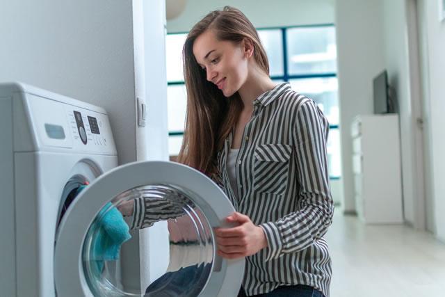 乾燥機に洗濯物を入れる女性