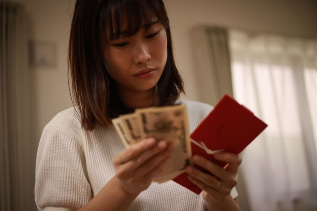 お金を片手に考え込む女性