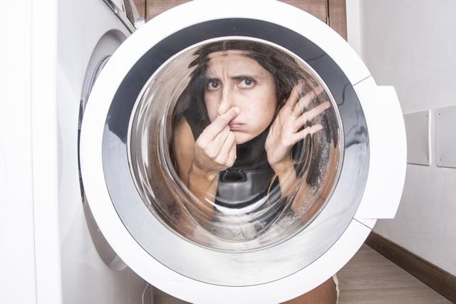 洗濯機が臭くて鼻をつまむ女性