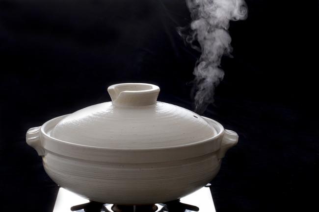コンロの上に置かれ湯気が出ている土鍋