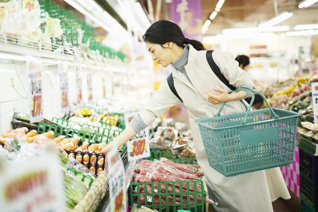 スーパーで野菜を選んでいる女性