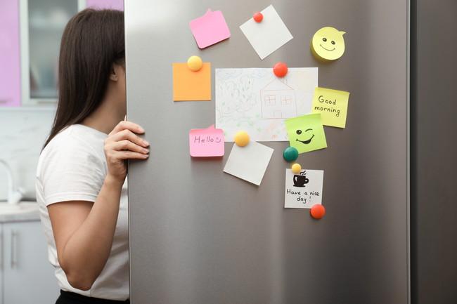扉にメモがたくさん貼られた冷蔵庫を開ける女性