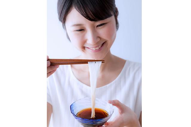 そーめんを食べる笑顔の女性