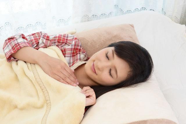 布団で寝ている女性