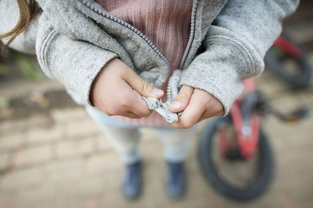 パーカーのジッパーを閉める子供の手