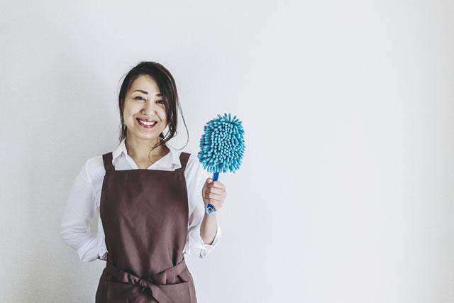 掃除道具を持った笑顔の女性