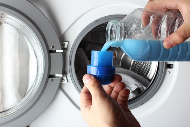 洗濯機に洗剤らしきものを入れる画