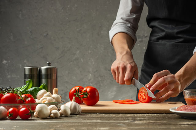 まな板でトマトを切る男性