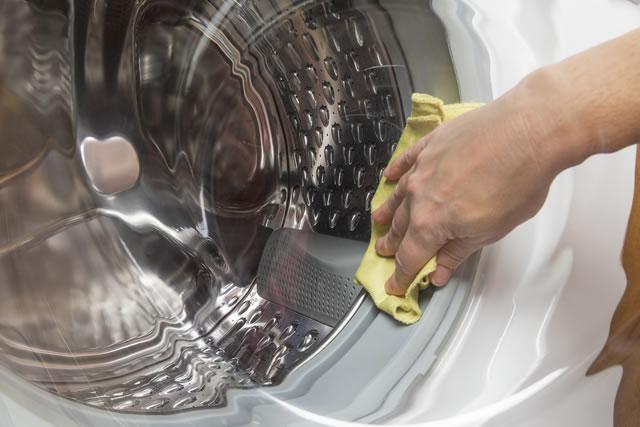洗濯機を拭いている手