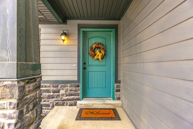 水色のドアとオレンジの玄関マット