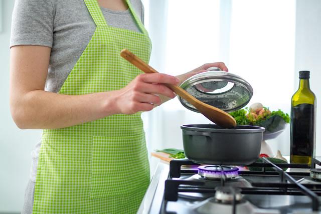 ガスコンロで料理をしている女性