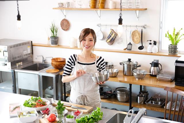 台所で楽しそうに料理する女性