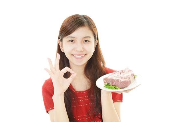肉を持ってOKする女性