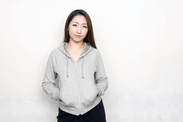 パーカーを着て壁際に立つ女性
