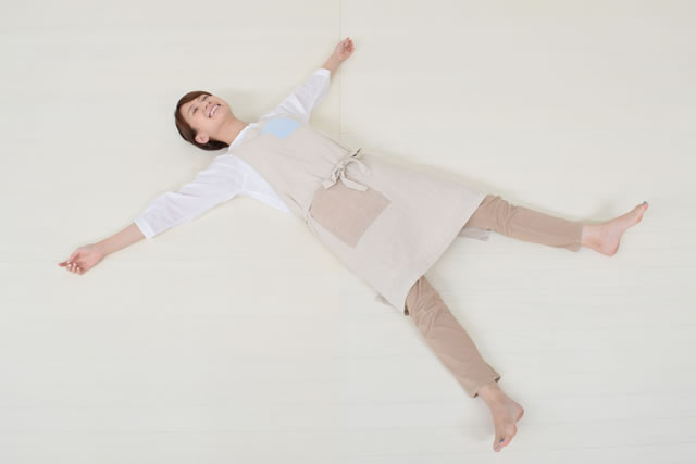 フローリングに寝転ぶ主婦