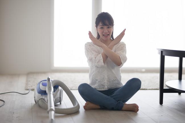 掃除機の横で×印をしている女性