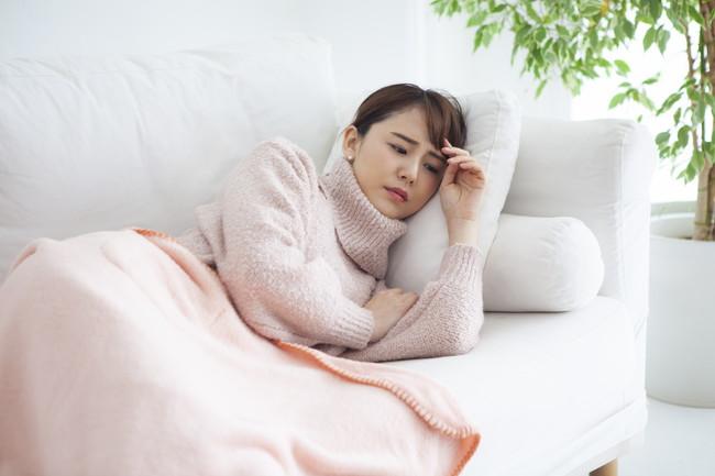 体調不良で横になっている女性