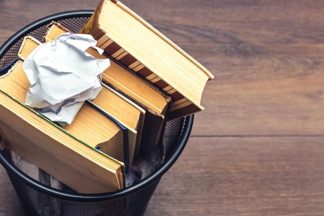 ゴミ箱に捨てられた本と丸められた紙