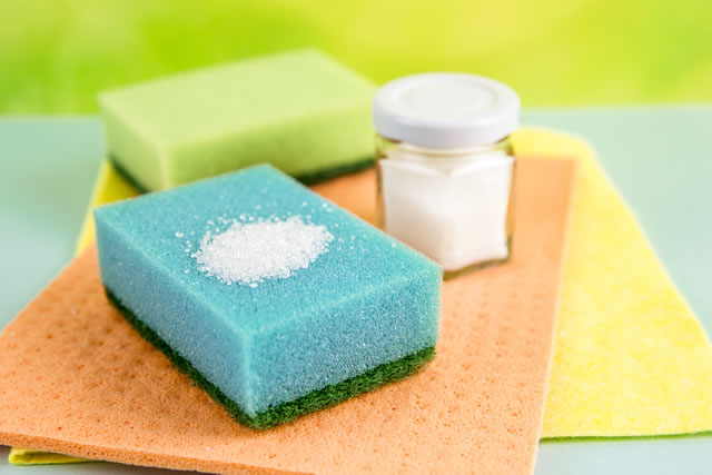 Natural organic citric acid cleaning products concept. White Citric acid powder on blue washing sponge and in jar. Green, orange and yellow washing sponge and textile cloth on blue background.